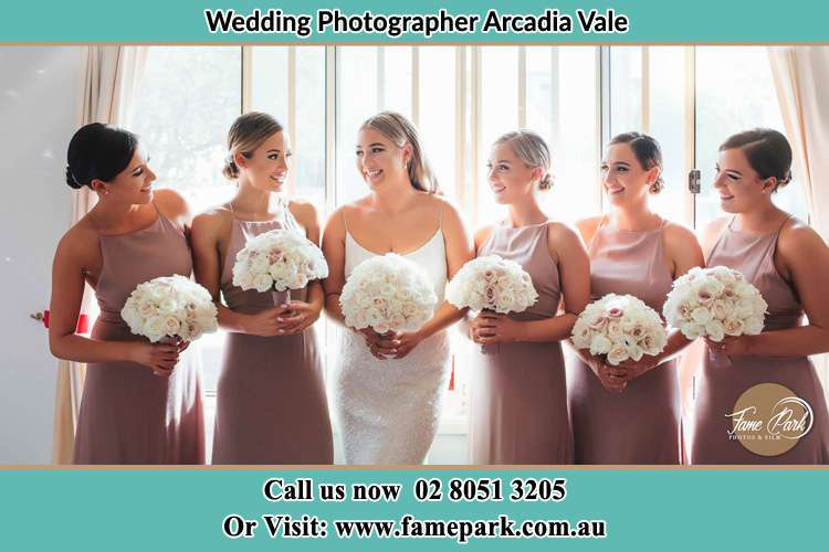Photo of the Bride and her bridesmaids each holding a bouquet of flowers Arcadia Vale