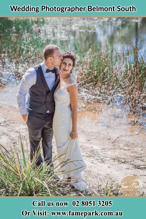 Photo of the Groom kiss the Bride near the lake Belmont South NSW 2280