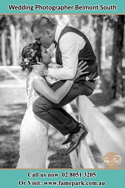 Photo of the Groom sitting on the fence while kissing the Bride on the forehead Belmont South NSW 2280