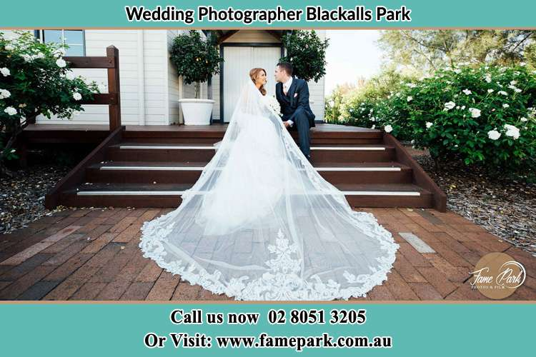 Photo of the Bride and the Groom looking each other while sitting at the staircase Blackalls Park NSW 2283