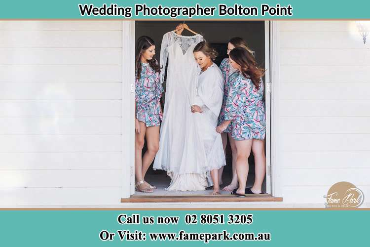 Photo of the Bride and the bridesmaids checking the wedding gown at the front door Bolton Point NSW 2283