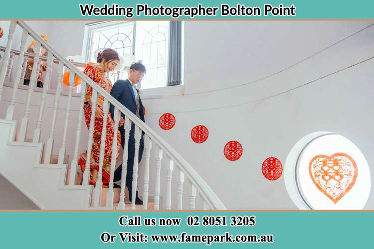 Photo of the Bride and the Groom walking down the stairs Bolton Point