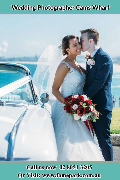 Photo of the Groom kiss the Bride besides the bridal car Cams Wharf NSW 2281