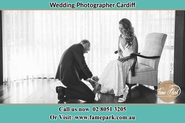The Bride is being helped by the Groom trying to put on her shoes Cardiff