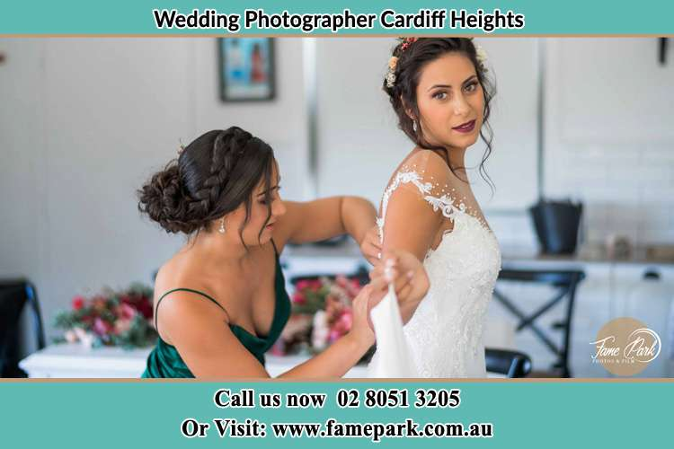 The Bride is being helped by bridesmaid trying to put her bridal gown Cardiff Heights