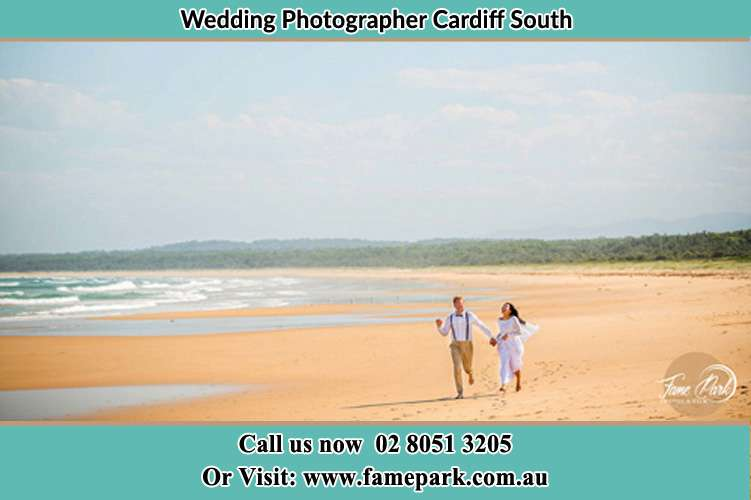 Photo of the Groom and the Bride walking at the sea shore Cardiff South NSW 2285