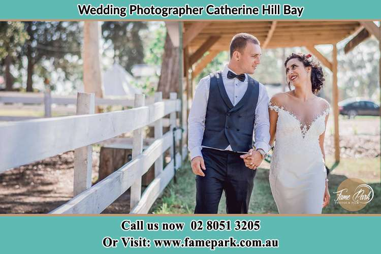 Photo of the Groom and the Bride holding their hands while walking Catherine Hill Bay