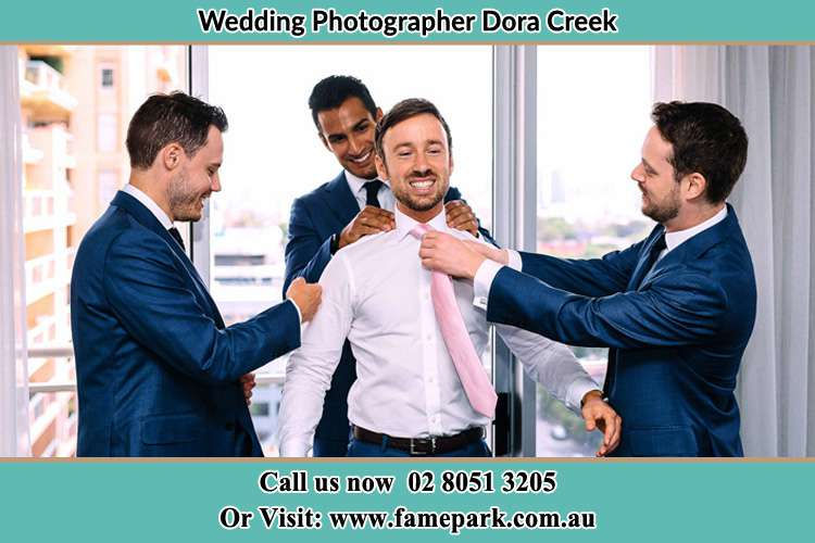 Photo of the Groom helping by the groomsmen getting ready Croudace Bay NSW 2280