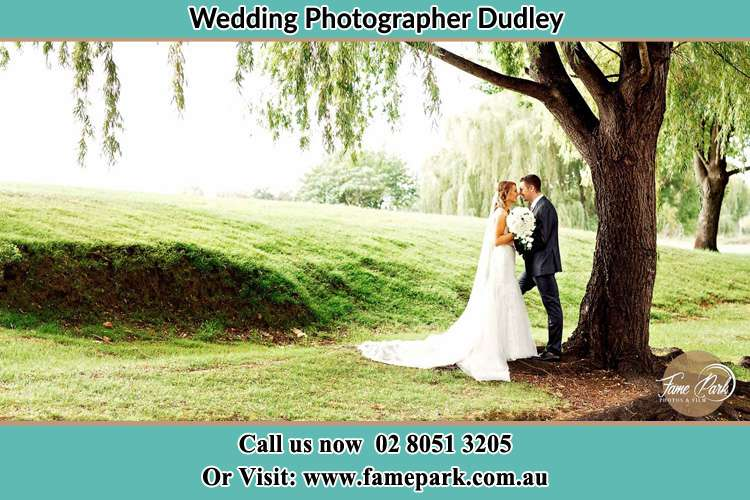 Photo of the Bride and the Groom kissing under the tree Dudley NSW 2290