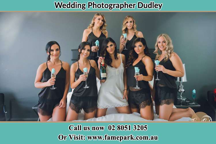 The bride holding a bottle of wine poses with the girls in front of camera Dudley