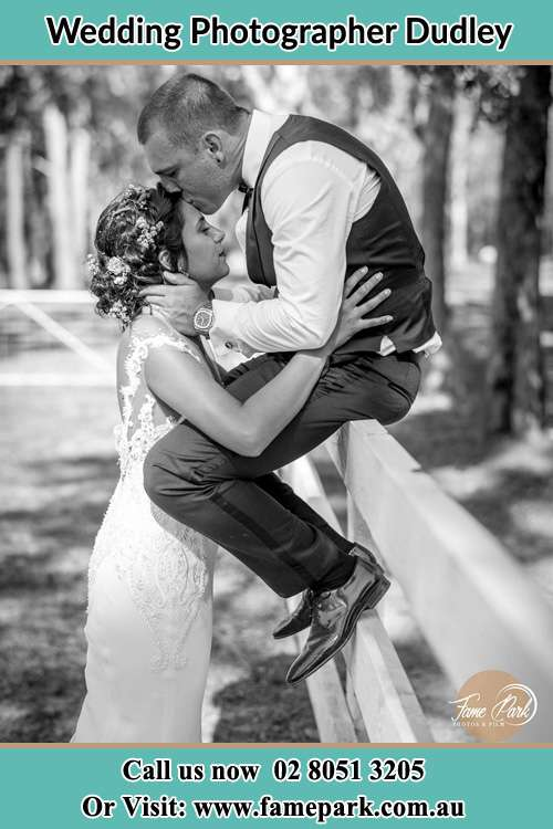 Photo of the Groom sitting on the fence while kissing the Bride on the forehead Dudley NSW 2290