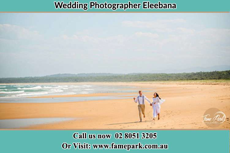 Photo of the Groom and the Bride walking at he shore Eleebana NSW 2282