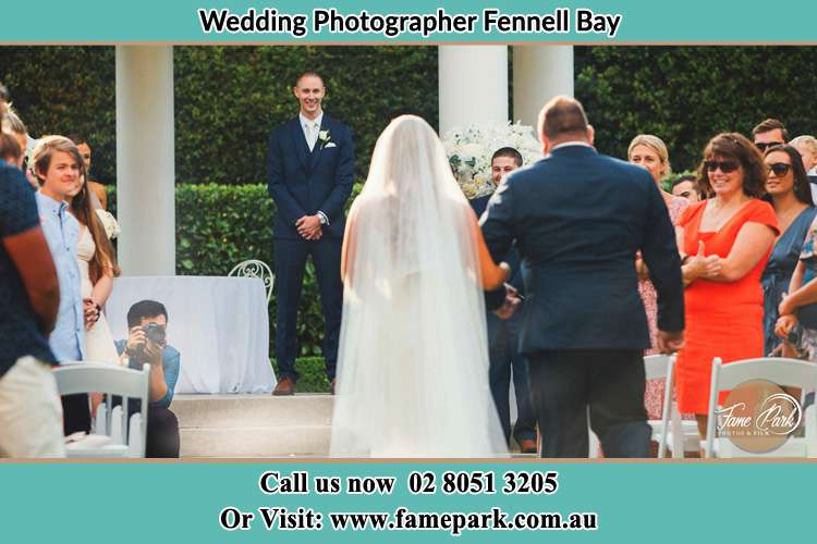 Photo of the Bride with her father walking towards to the waiting Groom Fennell Bay