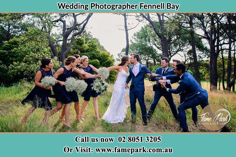 Photo of the Bride and the Groom kissing while teasing by the entourage Fennell Bay NSW 2283