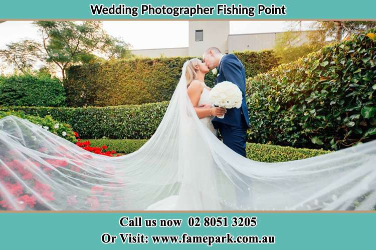 Photo of the newly weds kissing in the garden Fishing Point