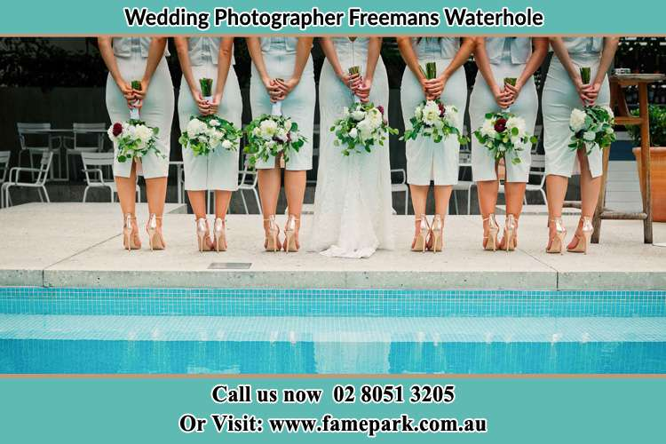Behind photo of the Bride and the bridesmaids holding flowers near the pool Freemans Waterhole NSW 2323