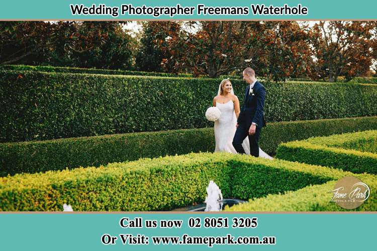 Photo of the Bride and Groom walking at the garden Freemans Waterhole