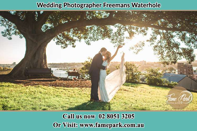 Photo of the new couple kissing under a big tree Freemans Waterhole
