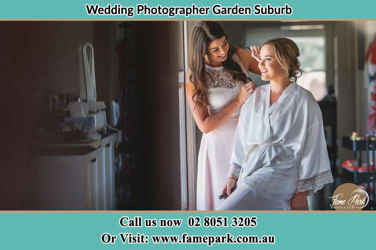 Photo of bridesmaid preparing the Bride for her wedding Garden Suburb