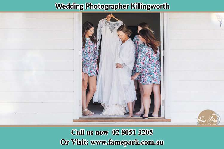 Photo of the Bride and the bridesmaids checking the wedding gown at the front door Killingworth NSW 2278