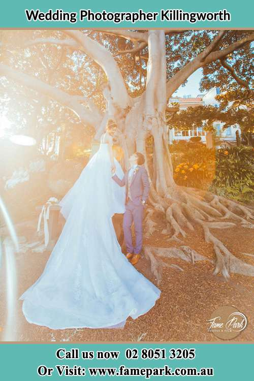 Photo of the Bride and the Groom looking each other besides the tree Killingworth NSW 2278