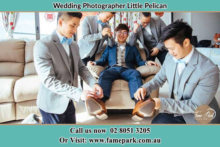 The Groom is being prepared for the wedding by his groomsmen Little Pelican