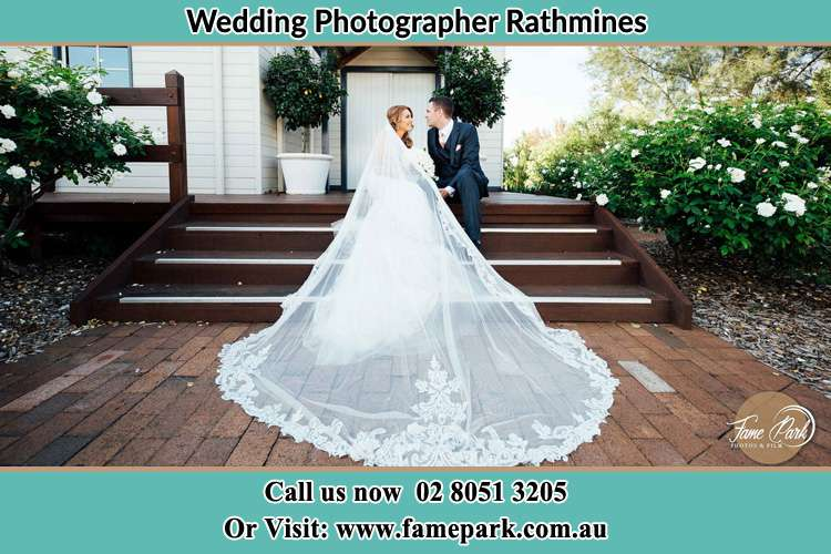 Photo of the Bride and the Groom looking each other while sitting at the staircase Rathmines NSW 2283