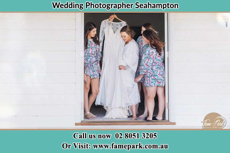 Photo of the Bride and the bridesmaids checking the wedding gown at the front door Seahampton NSW 2286
