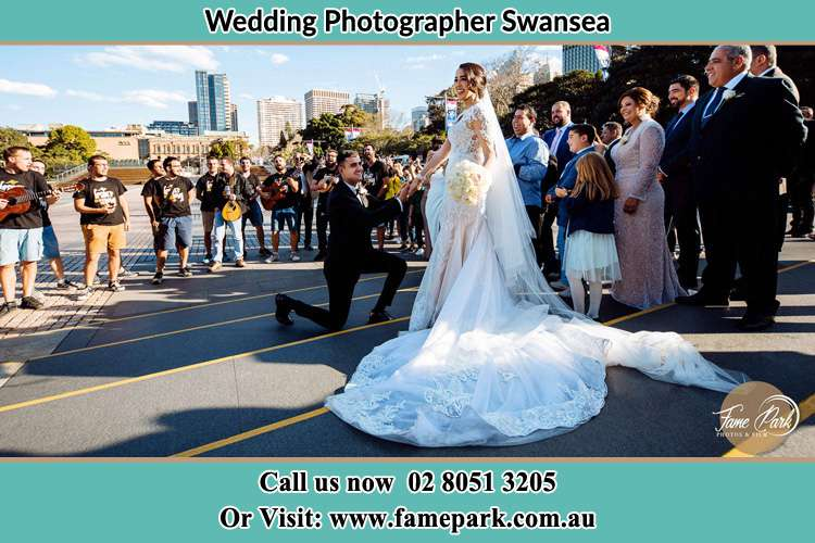 Photo of the Groom on his knee taking the Brides hand witnessing by the crowd Swansea 2281