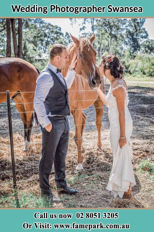Photo of the Bride give kiss to the horse and Groom looking at her Swansea 2281