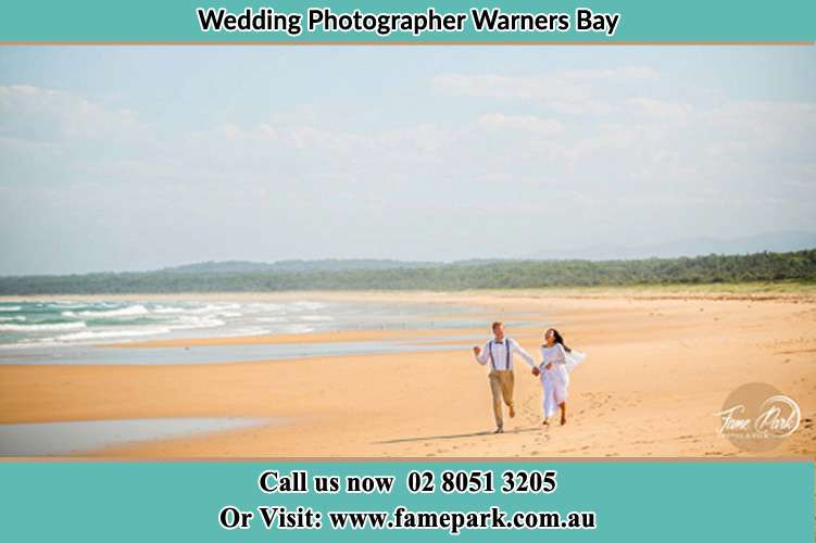 Photo of the Groom and the Bride walking at the sea shore Warners Bay NSW 2282