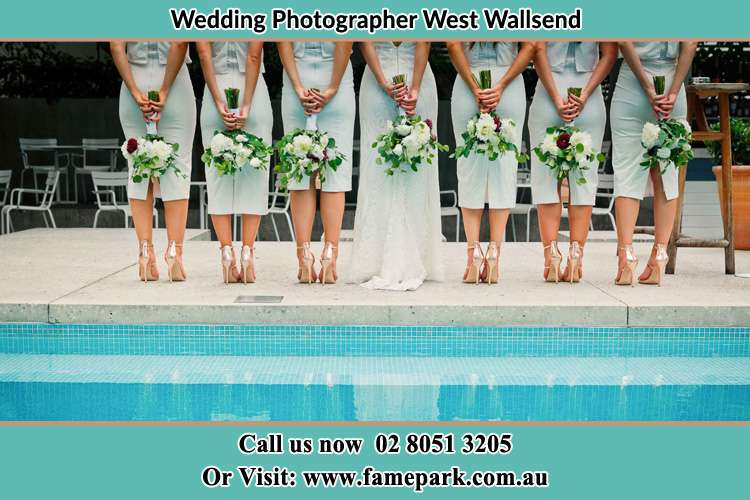 Behind photo of the Bride and the bridesmaids holding flowers near the pool West Wallsend NSW 2286